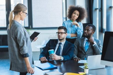 multicultural businesspeople looking at businesswoman with tablet in office