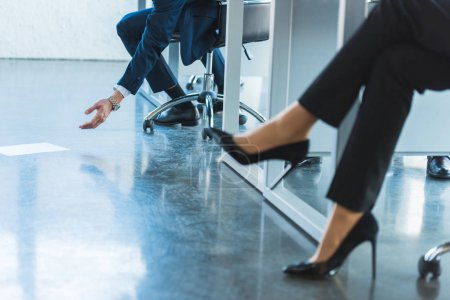 cropped image of businessman reaching for falling document