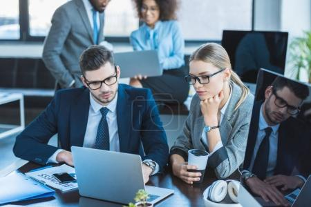 multicultural businesspeople looking at laptops in workspace