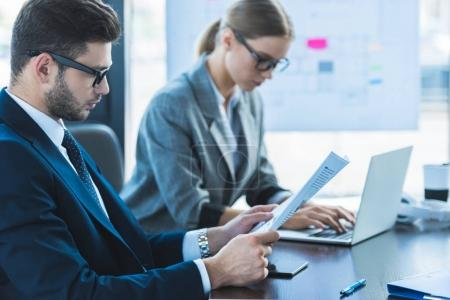 side view of businessman and businesswoman looking at documents in office