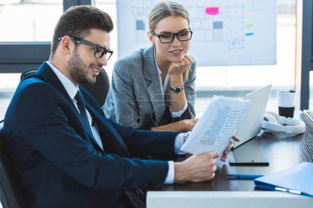 smiling businessman and businesswoman looking at documents in office