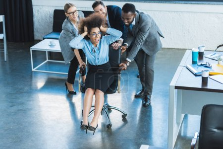 multicultural businesspeople having fun and racing colleague on chair in office