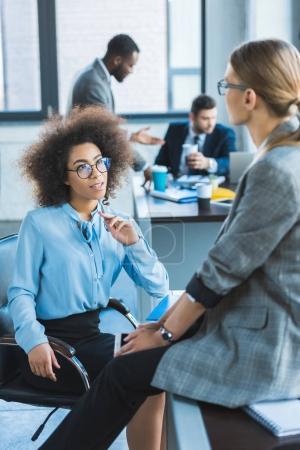 beautiful multiethnic businesswomen talking in office
