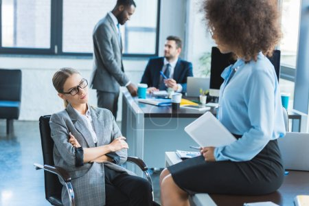multicultural businesswomen looking at each other in office