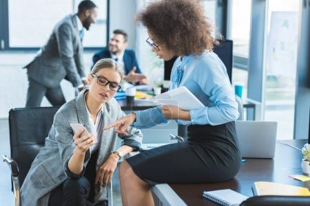multicultural businesswomen looking at smartphone in office