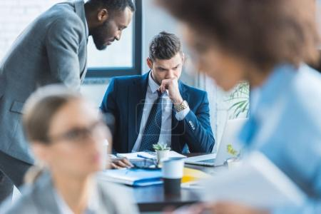 pensive multicultural businessmen at table in office
