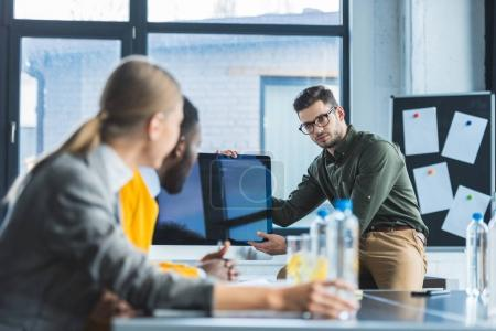 Photo for Multiethnic businesspeople looking at computer screen during meeting in office - Royalty Free Image