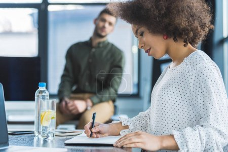 side view of african american businesswoman writing something in office