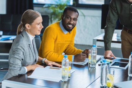 smiling multicultural businesspeople at table in workspace