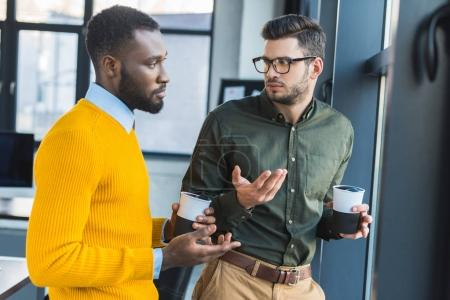 multicultural businessmen talking during coffee break in office