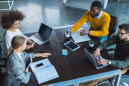 high angle view of multicultural businesspeople working with digital devices in office