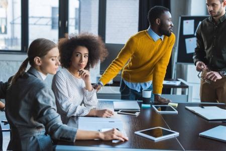 Photo pour Les gens d'affaires multiethniques au cours de la réunion dans le Bureau - image libre de droit