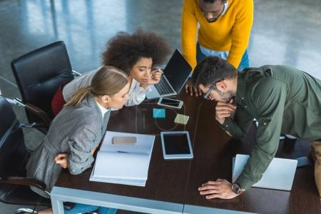 high angle view of multicultural businesspeople looking at tablet in office