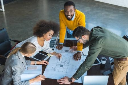 high angle view of multicultural businesspeople looking at blueprint in workspace