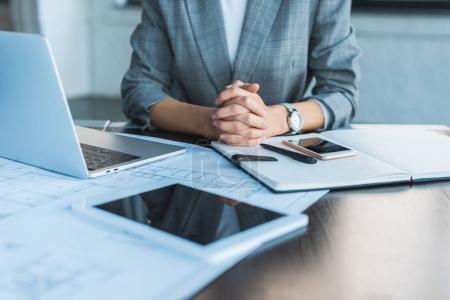 Photo pour Image recadrée d'une femme d'affaires assise à table au bureau avec des appareils numériques sur la table - image libre de droit