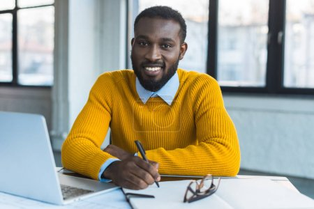 smiling african american businessman holding pen and looking at camera in office