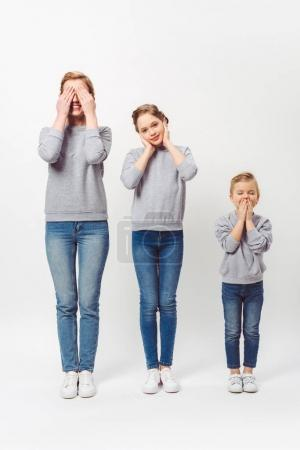 mother and daughters of different generations in similar clothing covering parts of faces isolated on grey