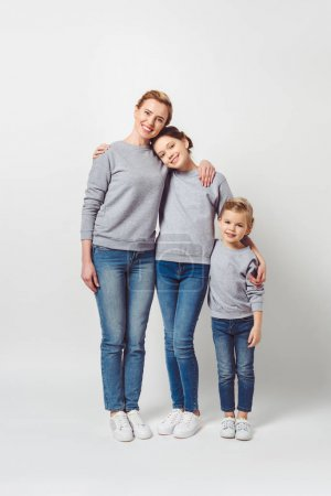 mother and daughters of different generations in similar clothing hugging each other isolated on grey