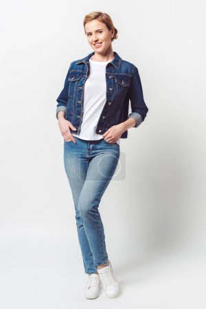 beautiful smiling woman in denim clothing looking at camera isolated on grey