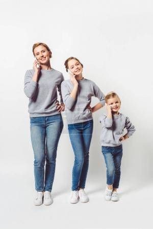mother and daughters in similar clothing talking on smartphones isolated on grey