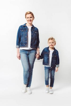 smiling mother and little daughter in similar denim clothing holding hands isolated on grey