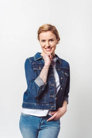 portrait of beautiful smiling woman in denim clothing looking at camera isolated on grey