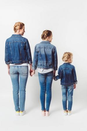 back view of family in similar denim clothing standing in row and holding hands isolated on grey