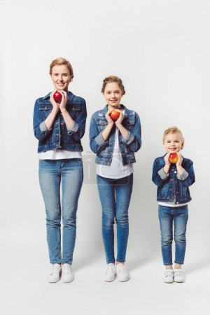 Photo for Smiling mother and daughters of different generations in similar clothing with fresh apples isolated on grey - Royalty Free Image
