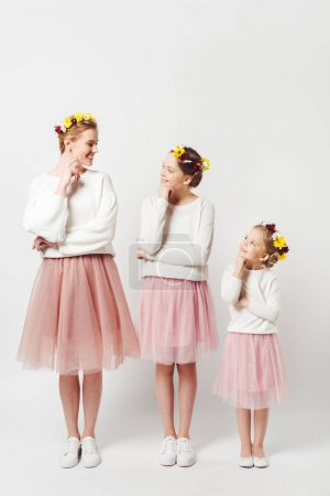 beautiful mother and daughters in similar clothing with floral wreathes on heads isolated on grey