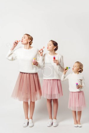 mother and daughter in similar clothing blowing soap bubbles together isolated on grey