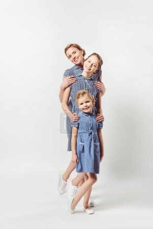 smiling mother and daughters in similar dresses isolated on grey