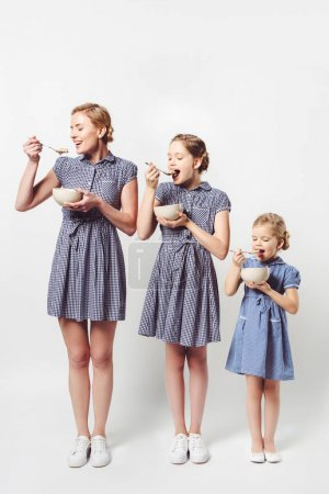 mother and daughters in similar dresses eating cereal breakfast together on white