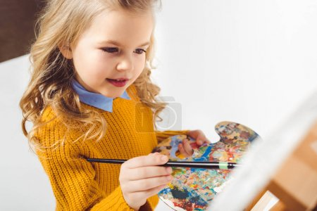 Photo for Close-up shot of little child painting on canvas with oil paint on white - Royalty Free Image