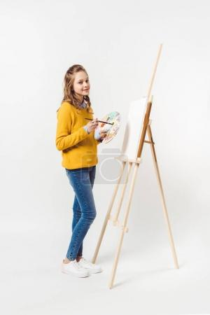 teen female painter with paint brush and palette near easel with blank canvas on white