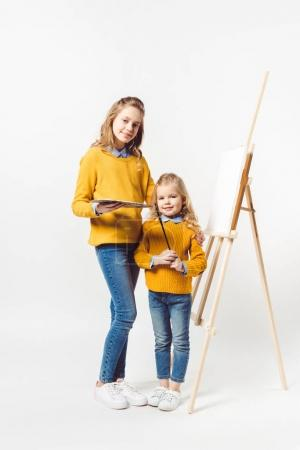 sisters of different generations with palette and paint brush standing in front of easel with blank canvas