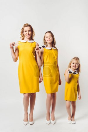 happy mother and daughters in similar retro style yellow dresses looking at camera on white