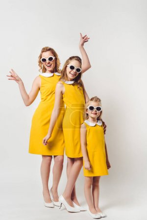 happy mother and daughters in similar retro style yellow dresses on white