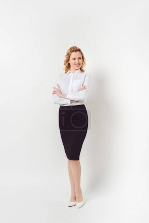 stylish businesswoman in white shirt with crossed arms on white