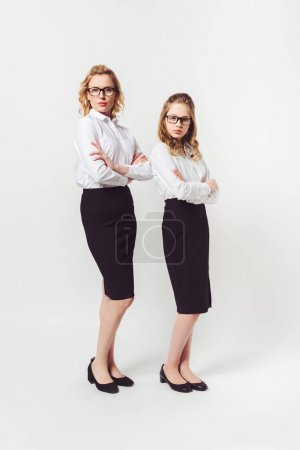 two businesswomen of different generations with folded arms on white