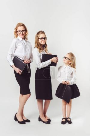 mother and daughters in similar businesswomen costumes with clutches on white