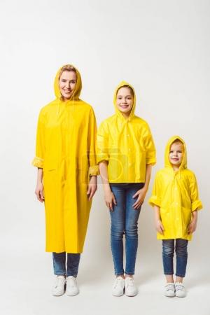 happy mother and daughters in yellow raincoats standing in row on white