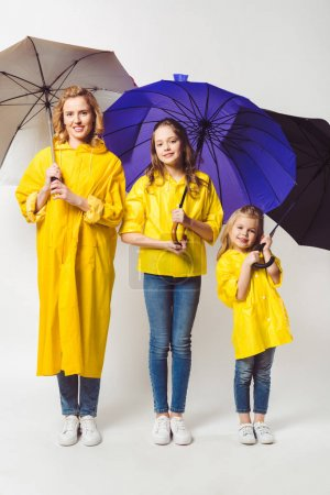 happy mother and daughters in yellow raincoats with umbrellas standing in row on white