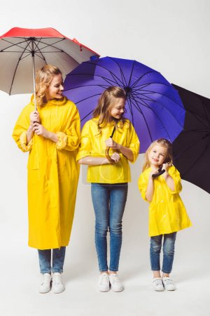 happy mother and daughters in yellow raincoats with umbrellas on white