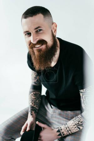 smiling bearded tattooed man looking at camera on white