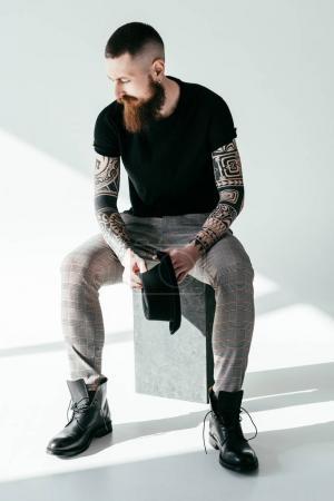 stylish bearded tattooed man sitting and holding hat on white