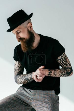 handsome bearded tattooed man with hat on white
