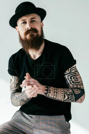 Photo for Handsome bearded tattooed man in hat looking at camera on white - Royalty Free Image