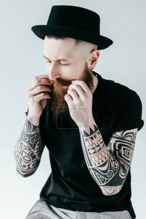 handsome bearded tattooed man twisting mustache isolated on white