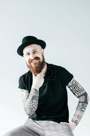 Foto de Sonriente a hombre tatuado tocar la barba y mirando a cámara aislada en blanco - Imagen libre de derechos