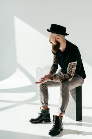 handsome bearded tattooed man sitting on white